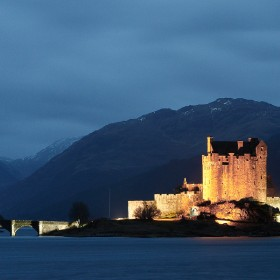 Eilean Donan Castle lit up at night with Beinn a'Chuirn acting as a backdrop.