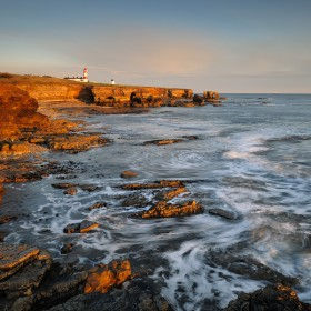 A lasting glow sweeps across these stunning limestone cliffs during sunrise along the Whitburn coast, England.