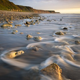 Receding waves reveal the rocky foreshore along Horden Coast during sunrise.