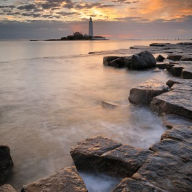 Dramatic, fiery skies reflect upon a rocky platform at St Mary's Lighthouse, Whitley Bay.